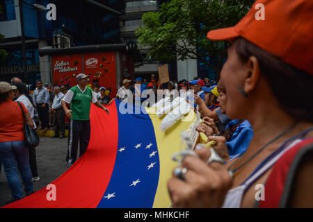 Caracas, Venezuela. 1st May 2018. Protesters seen holding a large Venezuelan flag during the demonstration. Workers and union leaders protested in the city of Caracas for better wages and better working conditions. In previous days, the president of the republic of Venezuela, Nicolas Maduro, decreed a minimum wage increase that is still below the inflation of the country and that does not cover the needs of the working class. Credit: SOPA Images Limited/Alamy Live News - Stock Photo