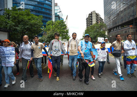 Caracas, Venezuela. 1st May 2018. Protesters seen marching during the demonstration. Workers and union leaders protested in the city of Caracas for better wages and better working conditions. In previous days, the president of the republic of Venezuela, Nicolas Maduro, decreed a minimum wage increase that is still below the inflation of the country and that does not cover the needs of the working class. Credit: SOPA Images Limited/Alamy Live News - Stock Photo