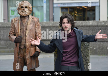 01 May 2018, Germany, Trier: Actor Tobias Schwieger (R) performing during the dress rehearsal of the piece «Marx! Love! Revolution!», a theatre piece by the Berlin author Johannes Kram, in front of the bronze statue of the old Karl Marx, represented by a masked extra. Photo: Harald Tittel/-/dpa - Stock Photo