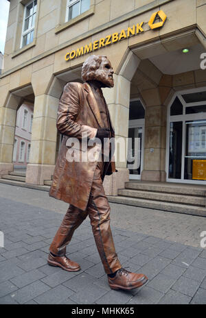 01 May 2018, Germany, Trier: An extra is dressed as the bronze statue of the old Karl Marx and walks from his plinth through the city as part of the dress rehearsal for the piece «Marx! Love! Revolution!», a theatre piece by the Berlin author Johannes Kram. Photo: Harald Tittel/-/dpa - Stock Photo