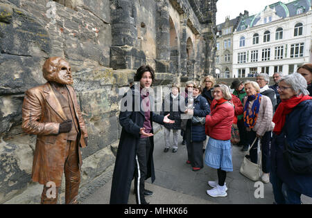 01 May 2018, Germany, Trier: Actor Tobias Schwieger (R) performing during the dress rehearsal of the piece «Marx! Love! Revolution!», a theatre piece by the Berlin author Johannes Kram, in front of the bronze statue of the old Karl Marx, represented by a masked extra (L). Photo: Harald Tittel/-/dpa - Stock Photo