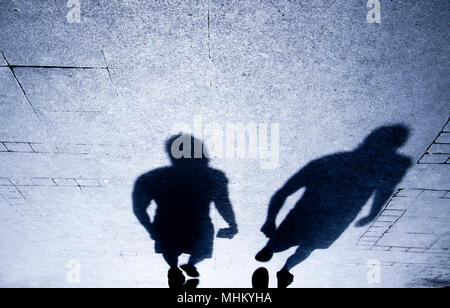 Blurry shadow and silhouette of people walking on the city street  sidewalk in the night - Stock Photo