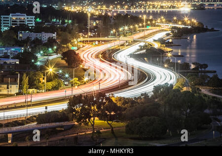 Light trails on a busy Mitchell Freeway at dusk. - Stock Photo
