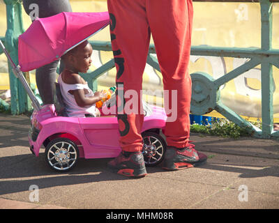 A young child in a pink toy car, on the Brighton seafront - Stock Photo