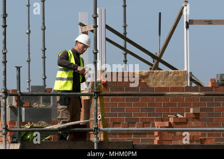 Bricklayer, site material, industrial bricklaying, occupation, building industry, cement, builder, worker, masonry, tool, mason, working on New build houses, Southport, Merseyside, UK - Stock Photo