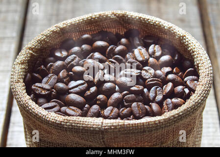 Close up fresh coffee beans keep in bag after blending on wood table. - Stock Photo