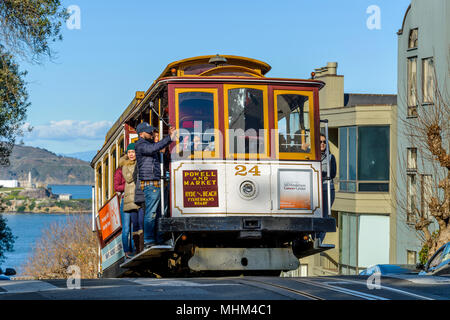 Street Cable Car - A cable car climbing up to the top of steep Russian Hill on Hyde St, with Alcatraz Island in background. San Francisco, CA, USA. - Stock Photo