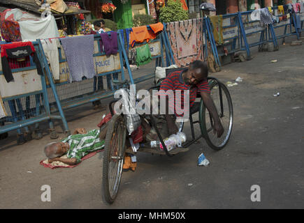bicycle rickshaw driver in Kolkata, India sleeping on his bike - Stock Photo