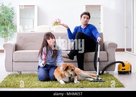 Husband cleaning house from dog fur - Stock Photo
