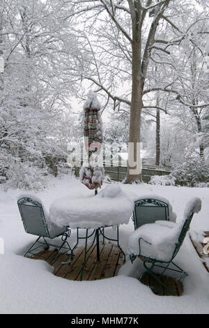 An outdoor backyard deck with furniture, planters, pots, umbrella, and garden vegetation heavily covered by a deep snow in winter - Stock Photo