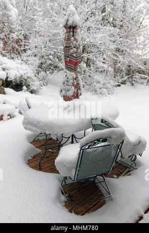 An outdoor deck with furniture, planters, pots and garden vegetation heavily covered by a deep snow in winter - Stock Photo