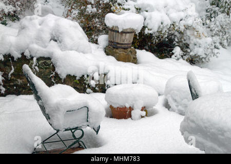 An outdoor patio winter wonderland, with furniture, planters, pots and garden vegetation heavily covered by deep snow in winter - Stock Photo