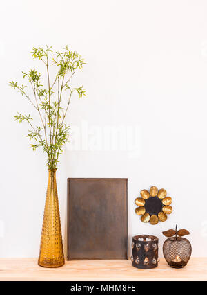 Home decor composition. Metal frame with copy space, glass vase with spring tree branches, mirror and antique candle holders. - Stock Photo