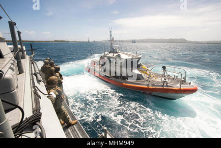A 47-foot Motor Lifeboat, assigned to U.S. Coast Guard Sector Guam, pulls alongside a Mark VI patrol boat, assigned to Coastal Riverine Group (CRG) 1, Det. Guam, during a towing exercise in Apra Harbor, Guam, March 28, 2018. CRG-1, Det. Guam is assigned to Commander, Task Force 75, the primary expeditionary task force responsible for planning and execution of coastal riverine operations, explosive ordnance disposal, diving engineering and construction, and underwater construction in the U.S. 7th Fleet area of operations. (U.S. Navy Combat Camera - Stock Photo