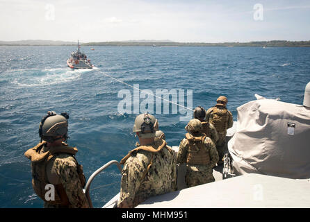 Sailors assigned to Coastal Riverine Squadron (CRS) 4, Det. Guam watch as their Mark VI patrol boat is towed by a 47-foot Motor Lifeboat, assigned to U.S. Coast Guard Sector Guam, during a towing exercise in Apra Harbor, Guam, March 28, 2018. CRS-4, Det. Guam is assigned to Commander, Task Force 75, the primary expeditionary task force responsible for planning and execution of coastal riverine operations, explosive ordnance disposal, diving engineering and construction, and underwater construction in the U.S. 7th Fleet area of operations. (U.S. Navy Combat Camera - Stock Photo