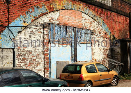 Cracked, peeling and flaking paint on wooden doors to railway arches used as workshops at Ardwick Greater Manchester England May 2018 - Stock Photo