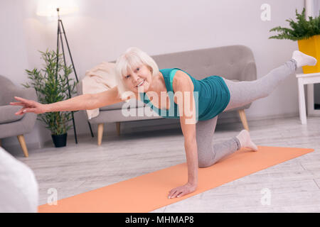 Pleasant senior woman standing on one knee and stretching - Stock Photo