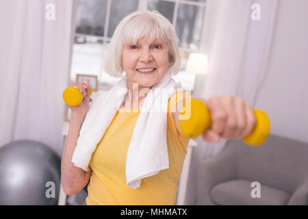 Joyful elderly woman exercising with dumbbells