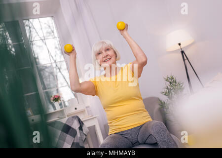 Charming senior woman smiling and lifting up dumbbells - Stock Photo