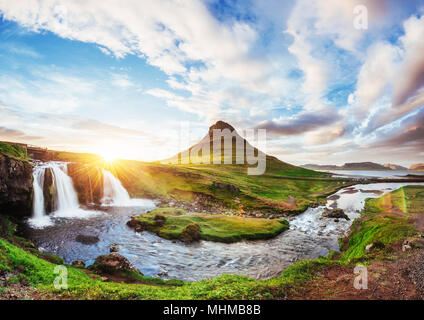The picturesque sunset over landscapes and waterfalls. Kirkjufell mountain, Iceland - Stock Photo