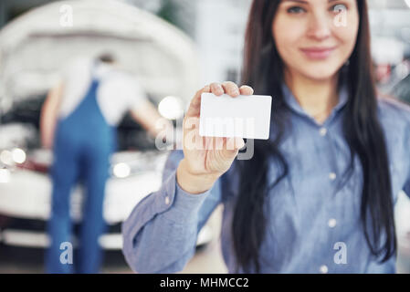 A beautiful woman keeps a business card of the car service center. The mechanic inspects the car under the hood in the background - Stock Photo