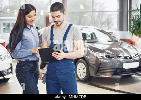 A man mechanic and woman customer discussing repairs done to her vehicle - Stock Photo