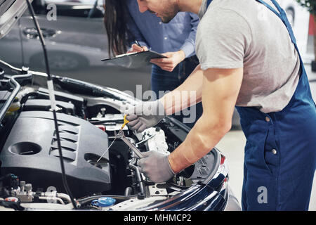 A man mechanic and woman customer look at the car hood and discuss repairs - Stock Photo