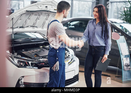 husband car mechanic and woman customer make an agreement on the repair of the car - Stock Photo