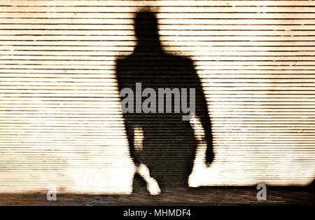 Blurry shadow silhouette of a man walking on patterned sidewalk - Stock Photo