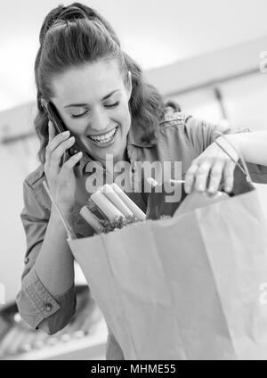Young housewife sort purchases after shopping and talking cell phone - Stock Photo