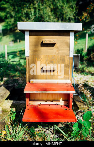 Wooden Frame Beehive in Organic Garden on a Sunny Day - Stock Photo