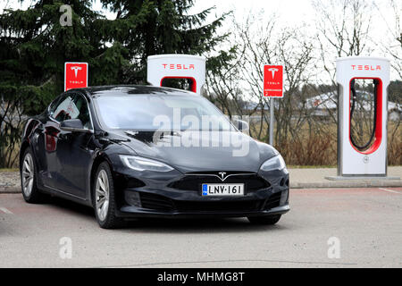 Black Tesla Model S electric car of the updated or facelift exterior design is charging battery at Supercharger station on a day of spring in Paimio,  - Stock Photo