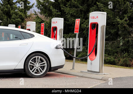 Side view detail of white Tesla Model S electric car connected and charging at Supercharger station on a day of spring in Paimio, Finland - April 28,  - Stock Photo