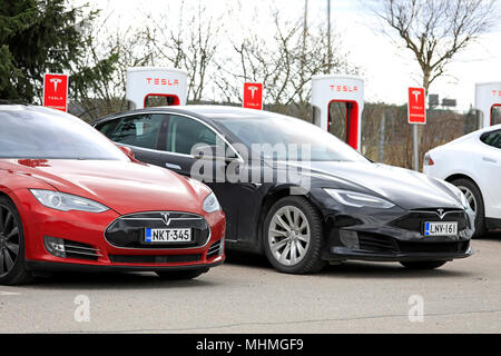 Two Tesla Model S electric cars, red of the previous design, black of updated design, are charging battery at Supercharger station on a day of spring  - Stock Photo