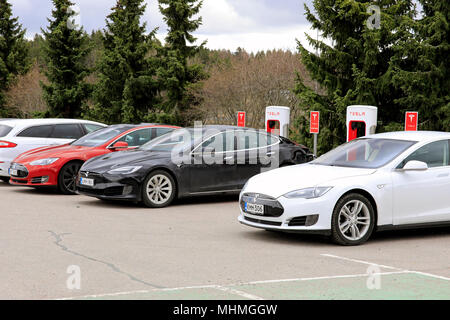 Three Tesla Model S electric cars are charging battery on a Supercharger station on a day of spring in Paimio, Finland - April 28, 2018. - Stock Photo