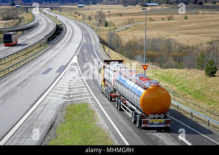 Tank truck drives on motorway ramp and takes caution at yield sign before entering the road on a clear day of spring. - Stock Photo