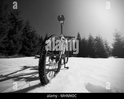 Cycling in winter snowy mountains on large tire wheels mountain bike. Sunny winter day. - Stock Photo