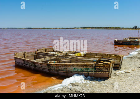 Wooden boat on the coast of the pink lake in Senegal called Lake Retba or Lac Rose - Stock Photo