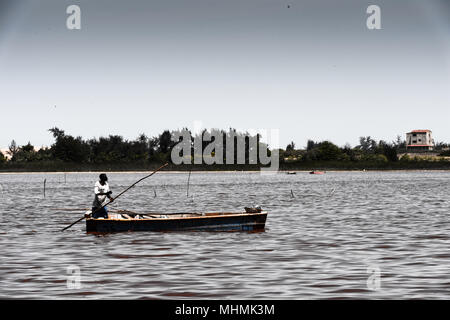 African man sails on the boat over the pink lake - Stock Photo