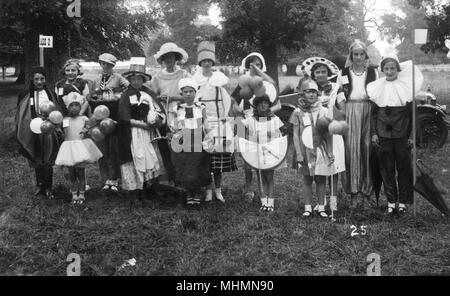 A group of children in fancy dress at a fete or carnival.  Among the costumes are a clown, a Welsh girl and a harem girl.       Date: c,1928 - Stock Photo