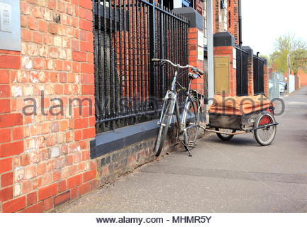 A Bicycle With Trailer Parked On Its Stand By Railings To A Building In Ardwick Greater Manchester May 2018 - Stock Photo