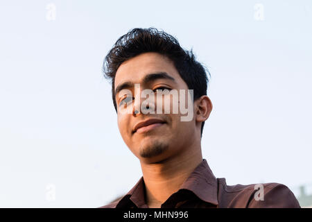 Dhaka, Bangladesh, February 24 2017: Portrait of a smiling young Bangladeshi man with a brown shirt in the evening light taken from below - Stock Photo