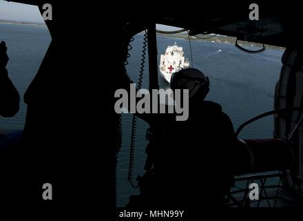 180427-N-MD713-0317TRINCOMOLEE, Sri Lanka (April 27, 2018) Naval Air crewman (helicopter) 3rd Class Daniel Lewis, assigned to the 'Wildcards' of Helicopter Sea Combat Squadron (HSC) 23, looks out the door of an MH-60S Sea Hawk helicopter as prepares to land on Military Sealift Command hospital ship USNS Mercy (T-AH 19) during a humanitarian and disaster relief exercise in support of Pacific Partnership 2018 (PP18), April 27, 2018. PP18's mission is to work collectively with host and partner nations to enhance regional interoperability and disaster response capabilities, increase stability and  - Stock Photo
