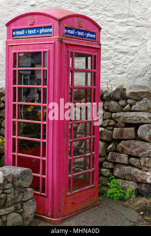 Old fashioned red telephone box offering e-mail text and phone services - Stock Photo