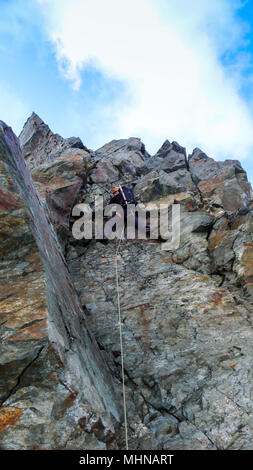 mountain climber climbing a steep rock wall on his way to a high alpine summit - Stock Photo