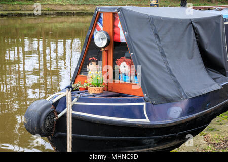 Old fashioned canal narrowboat with a canvas cover.  On the Macclesfield canal the narrow boat has a tarpaulin covered roof.  Toys are in the windows - Stock Photo