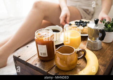 Cozy breakfast scene in bed with waffles on a sunny weekend - Stock Photo