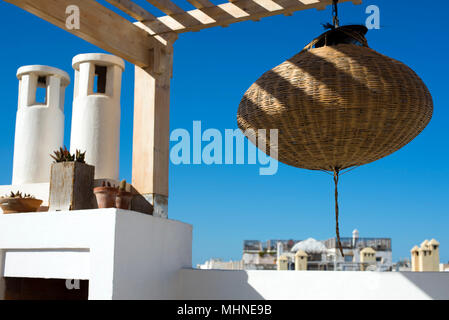 Rattan lampshade hangs on a roof top terrace overlooking the medina old town of  Essaouira, Morocco, Africa. - Stock Photo