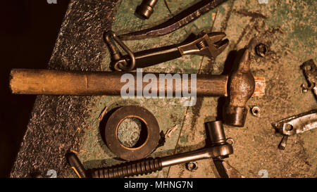 Still life of old hand tools. On the dirty table lie a hammer, electrical tape, wrench, pliers, nut, and other tools. - Stock Photo