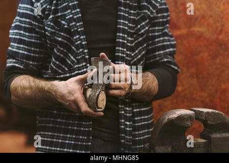 Man working in carpentry workshop. He checks sharpness of ax blade. Men at work. Hand work. - Stock Photo